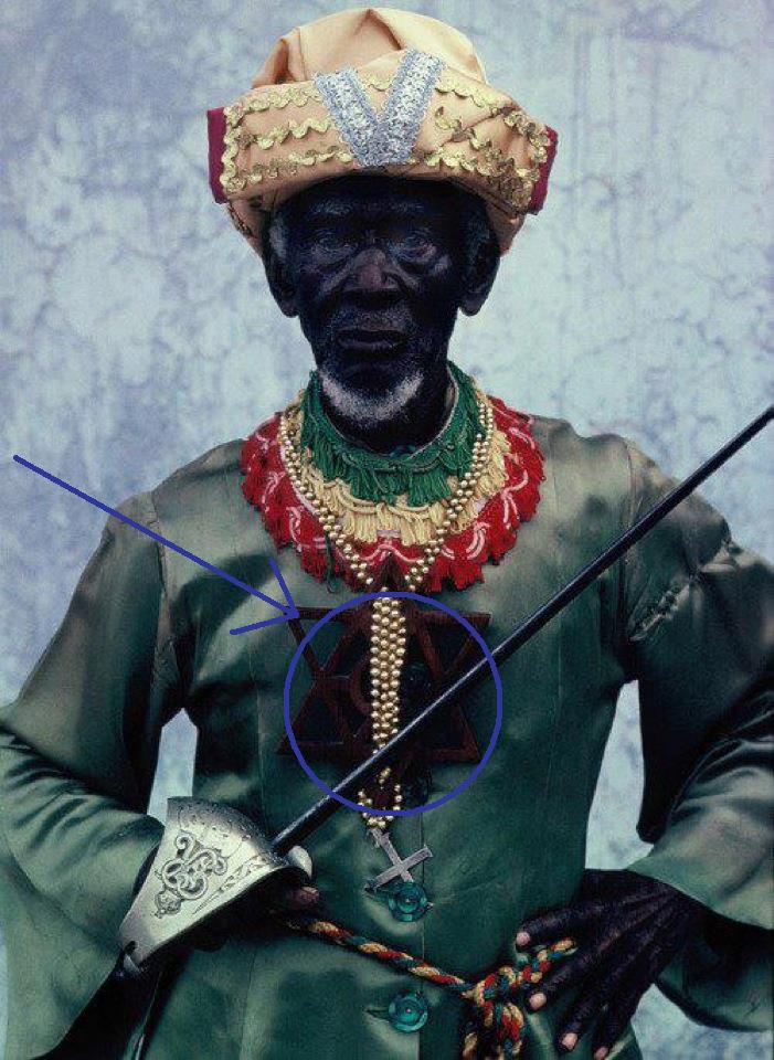 -one/third of the Ras Tafari founders, proudly sporting an array of what seems to be Moorish garbs, with Ethiopian Bandera colors adorning his neck; along with a cross & Magen David/cross fusion. (a symbol very prevalent from the East)