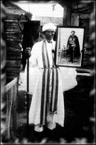 Prince Emmanuel in Priestly garb(Shepheard) with a photo of H.I.M.